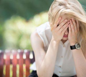 sorglig blond kvinna som håller händerna i ansiktet