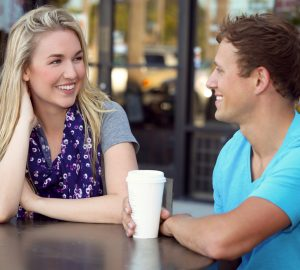 ett ungt leende par över kaffe som pratar