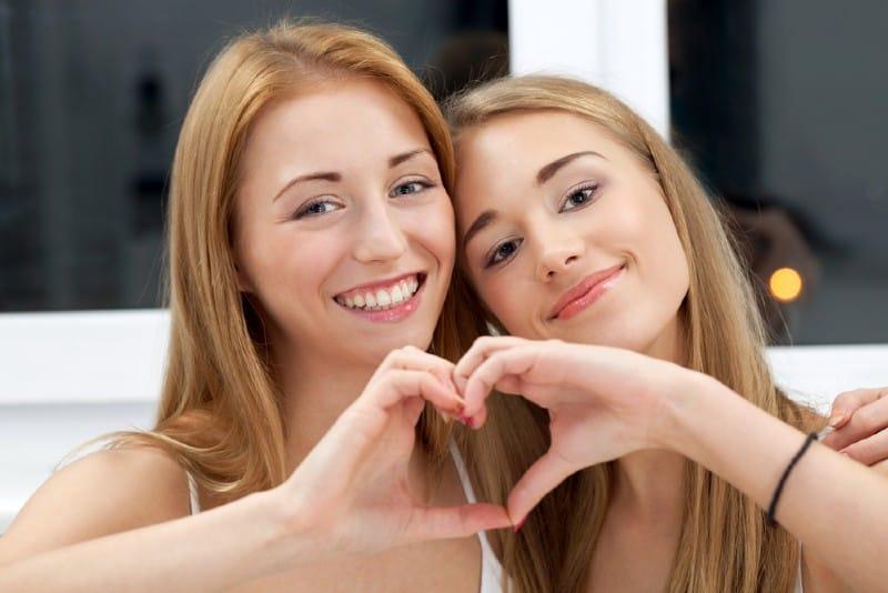 Två bästa vänner som visar hjärtaform med händer