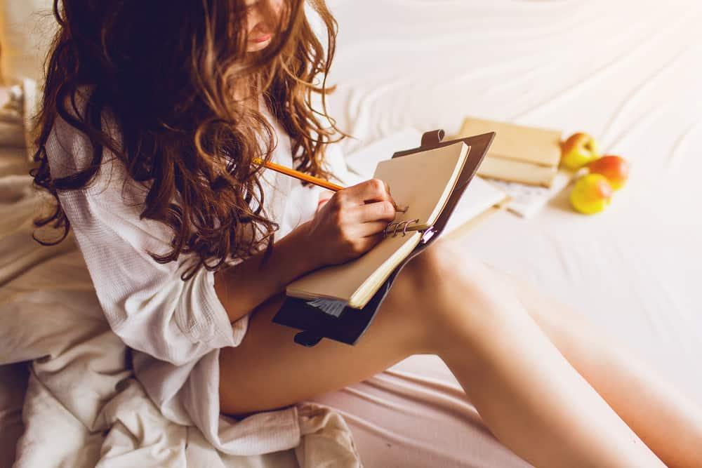 bild av ganska ung kvinna som sitter på sin mysiga säng och gör anteckningar