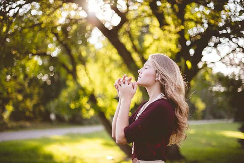 blond kvinna med stängda ögon ensam i naturen