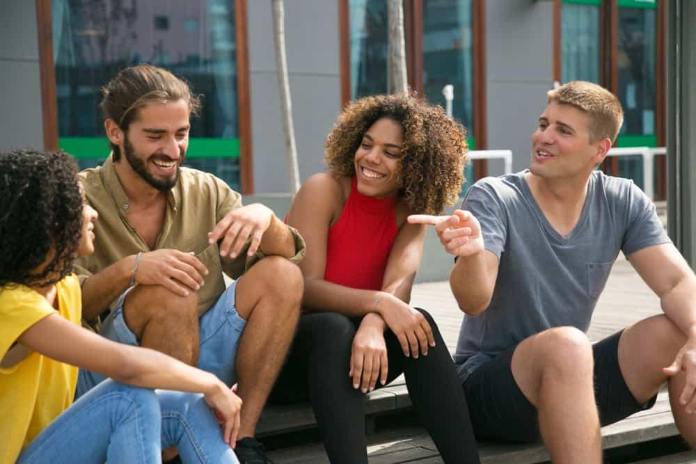 en grupp unga män och kvinnor sitter på trappan och skämt