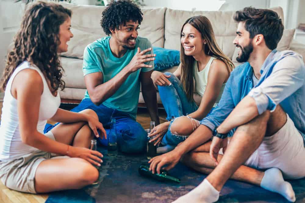 en grupp vänner med en öl sitter på golvet och spelar ett spel med sanning eller utmaning