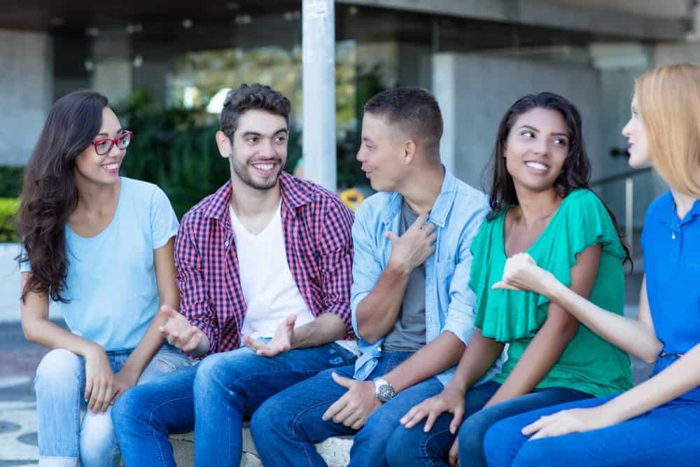 en grupp vänner sitter utanför och pratar