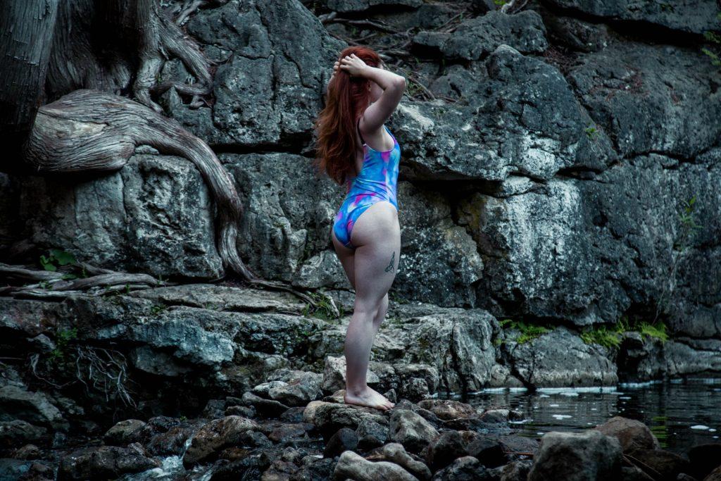 en kvinna i baddräkt står på en sten