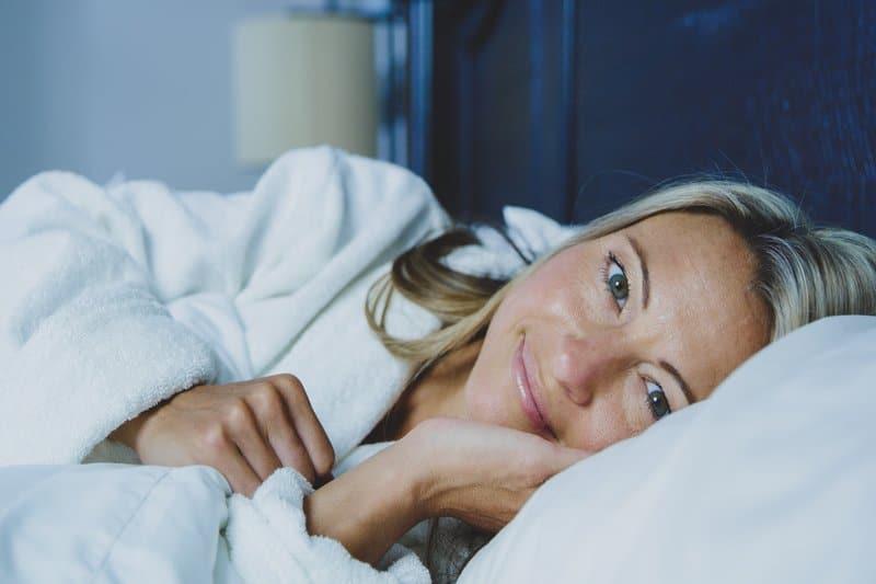 en kvinna i en kram ligger i sängen