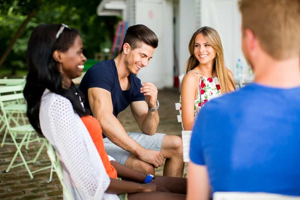 en leende grupp vänner som sitter och pratar