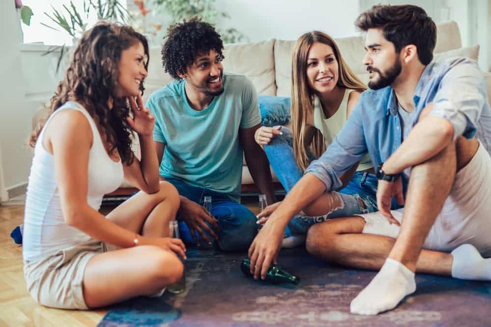 en man med skägg vänder en flaska och spelar en sanning eller en utmaning medan hans vänner håller noga med honom
