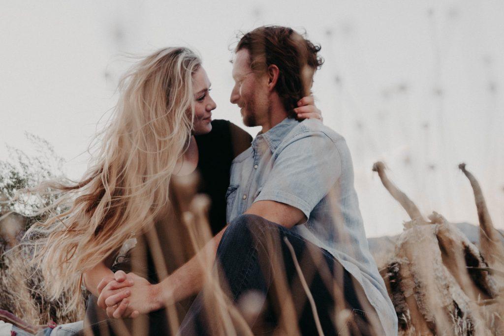 en man och en kvinna sitter i gräset omfamnar