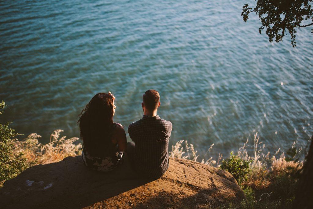 en man och en kvinna som sitter på en klippa
