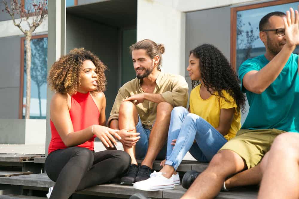 en svart kvinna i en rosa t-shirt berättar för sina vänner en rolig historia