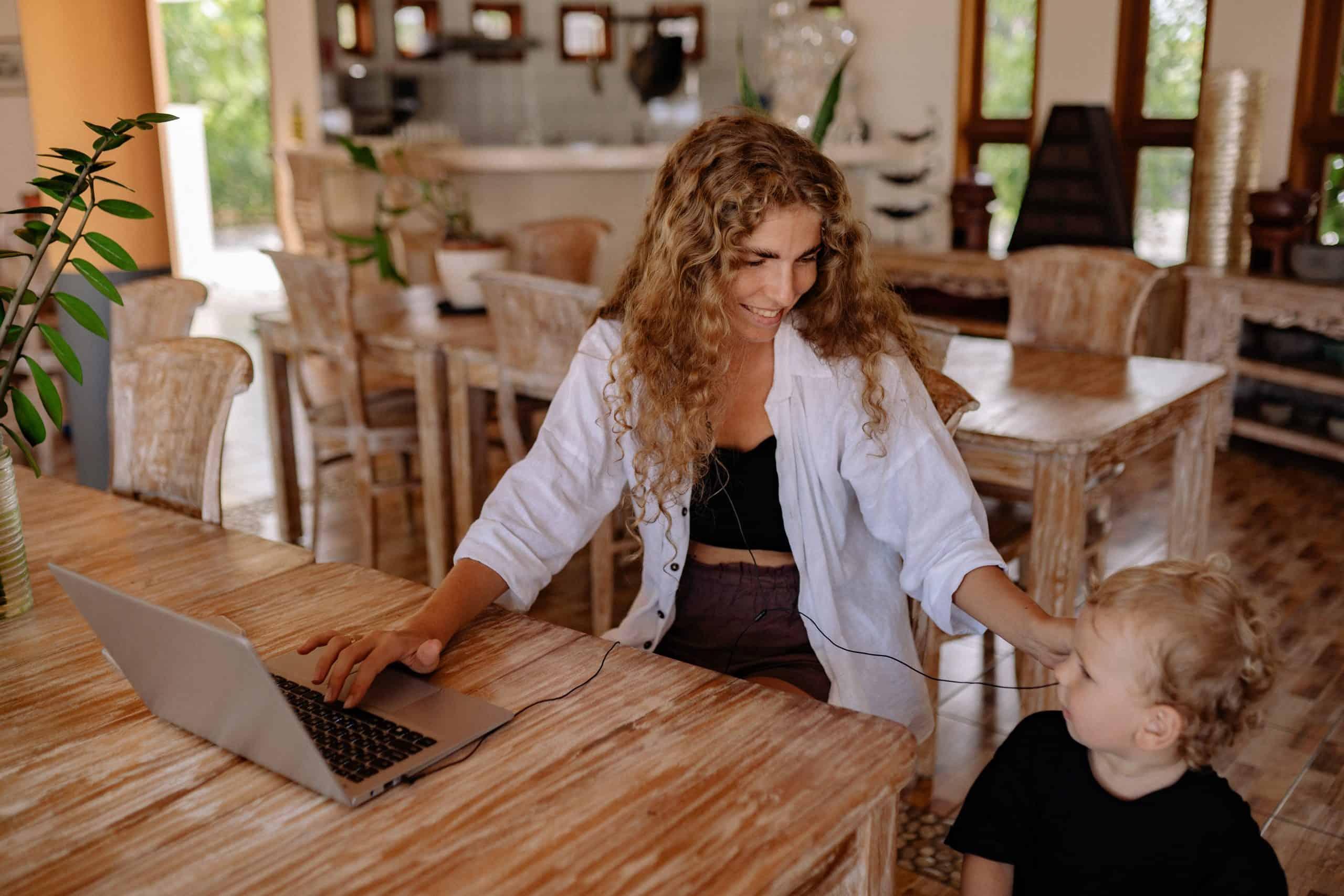 foto av kvinna som ler medan man sitter vid bordet med barnet