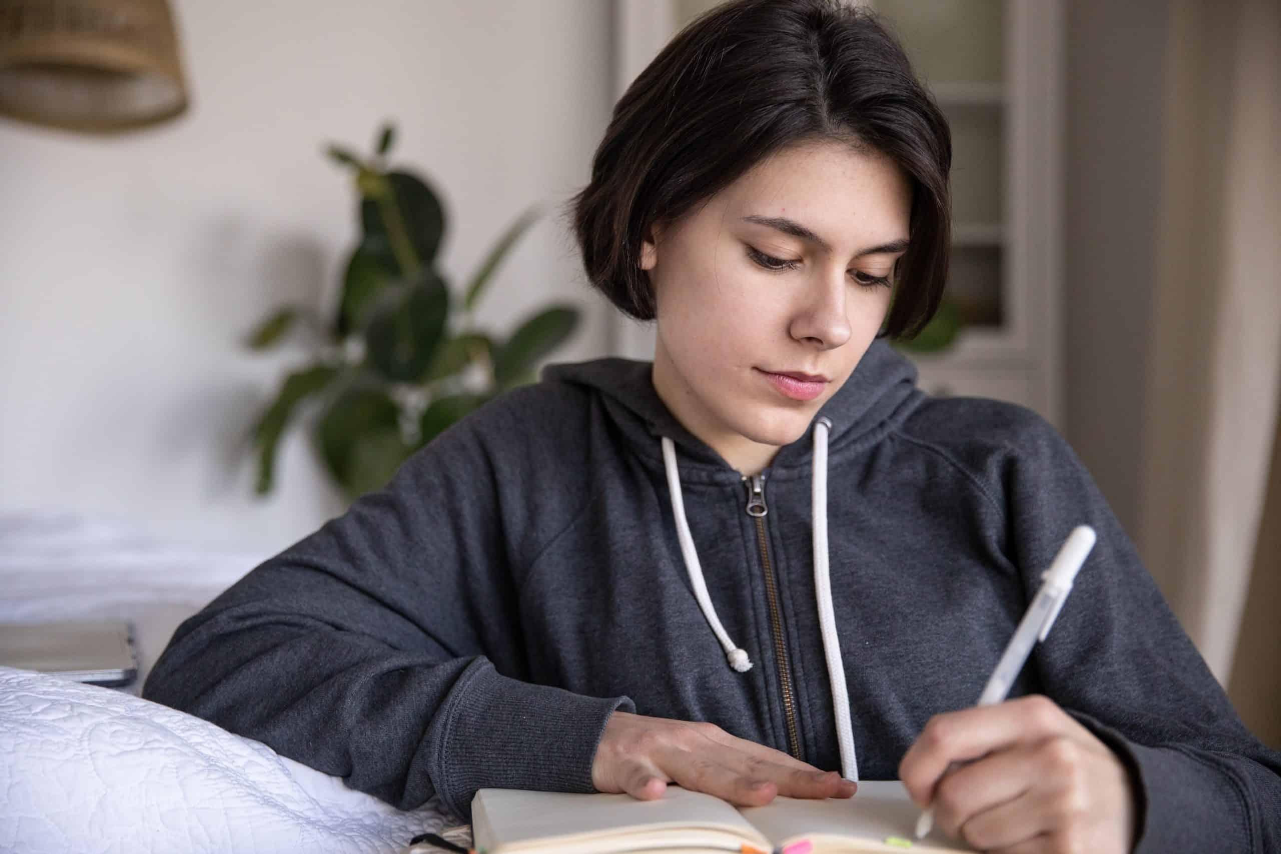 foto av kvinna som skriver på en anteckningsbok