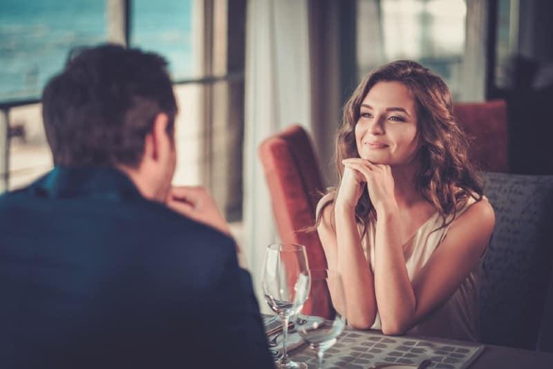 man och kvinna sitter ansikte mot ansikte vid ett bord
