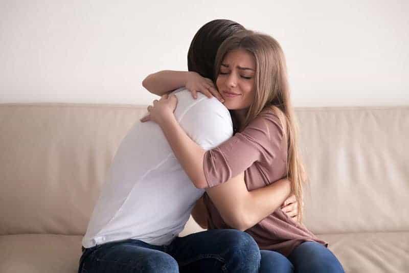 känslomässiga par som kramar på soffan