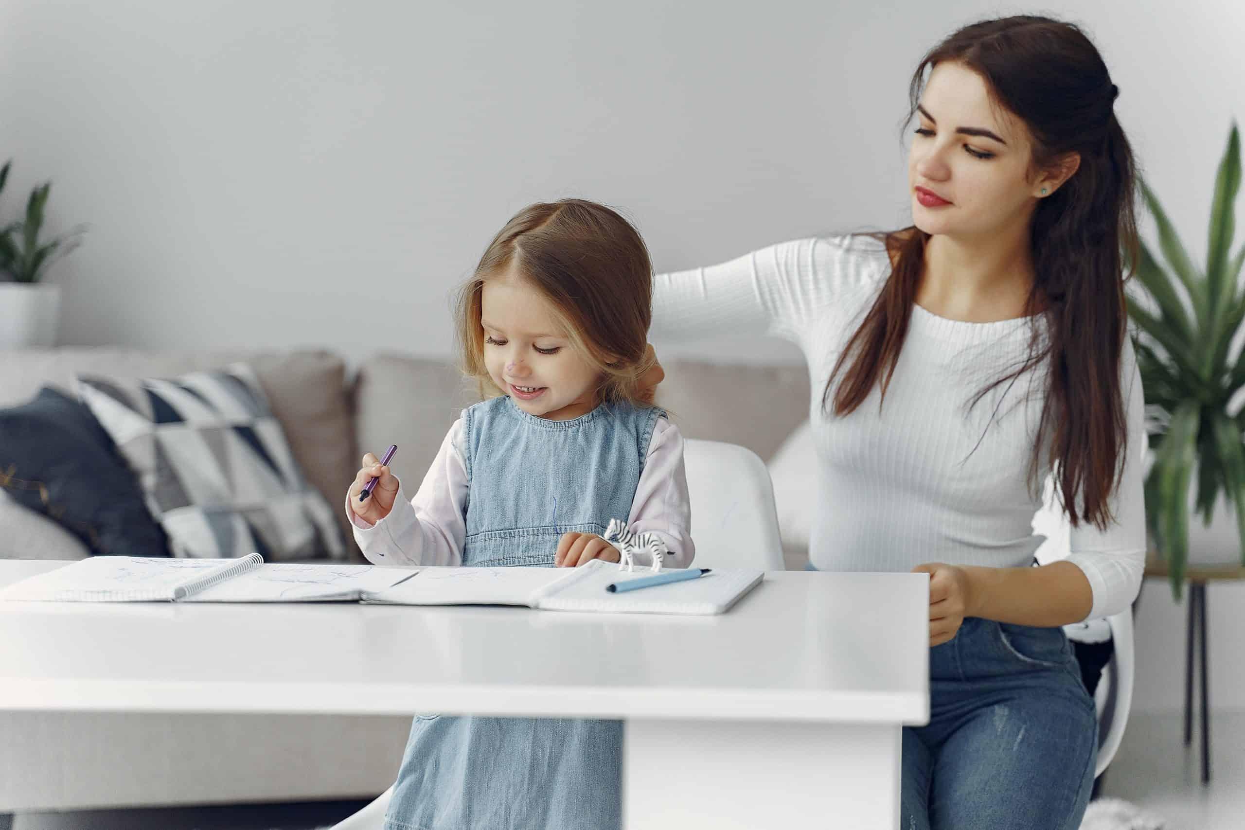 kvinna fixar barnets hår medan hon skriver
