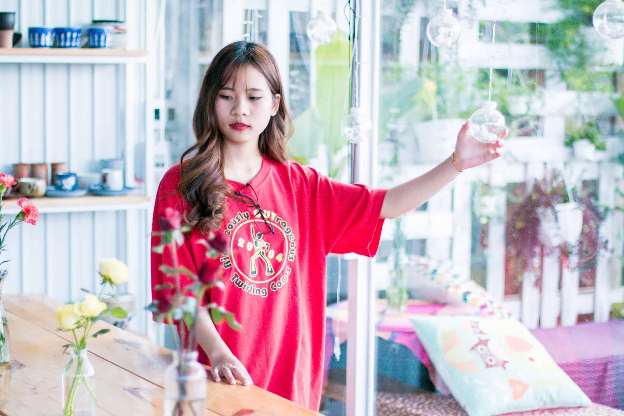 kvinna i röd skjorta ser på rosor på bordet