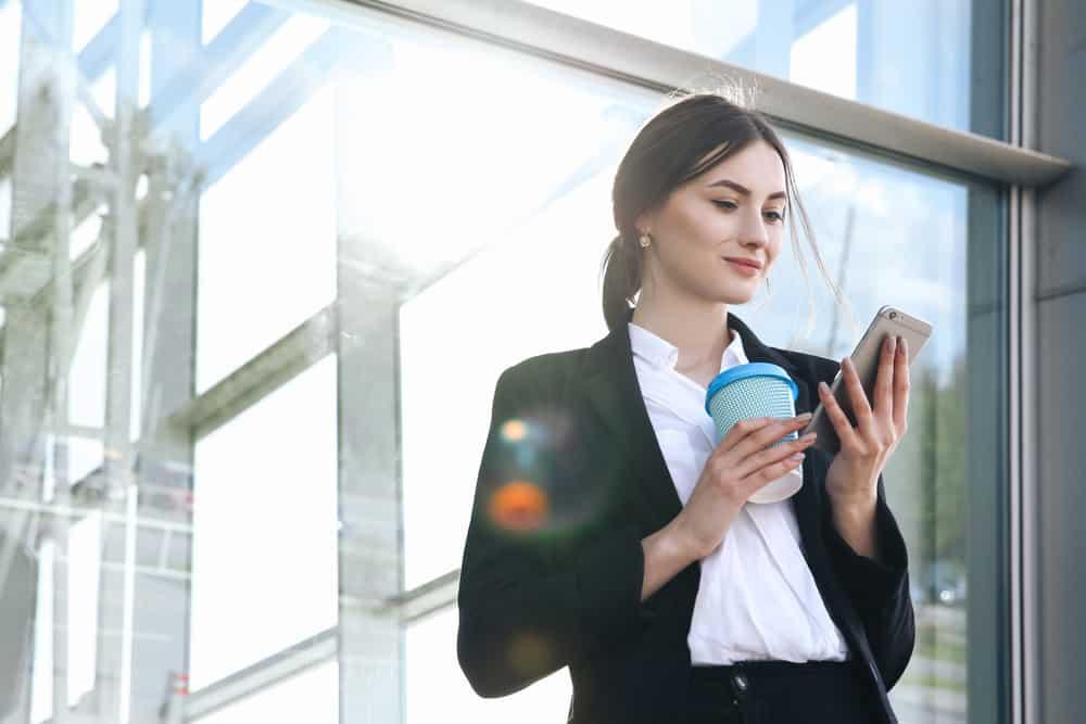 kvinna med kaffe och prata i telefon nära kontoret