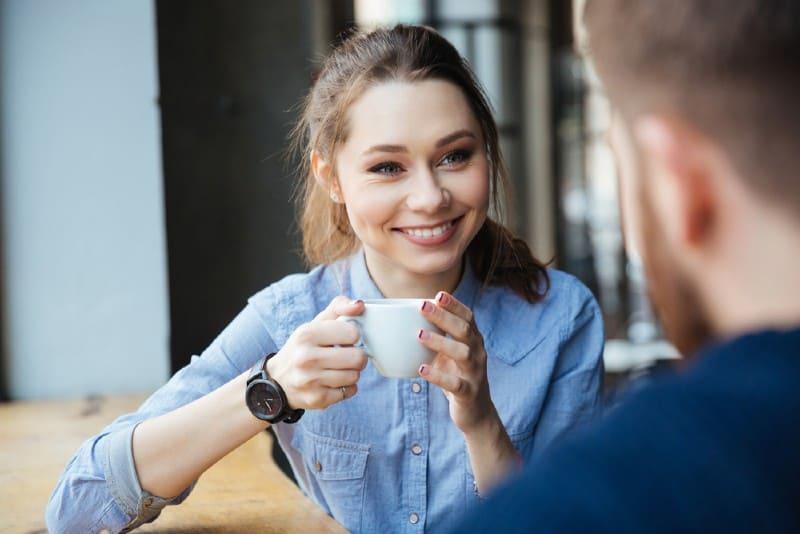 Ung nätt gladlynt kvinna som sitter och dricker kaffe i kafé med den skäggiga mannen