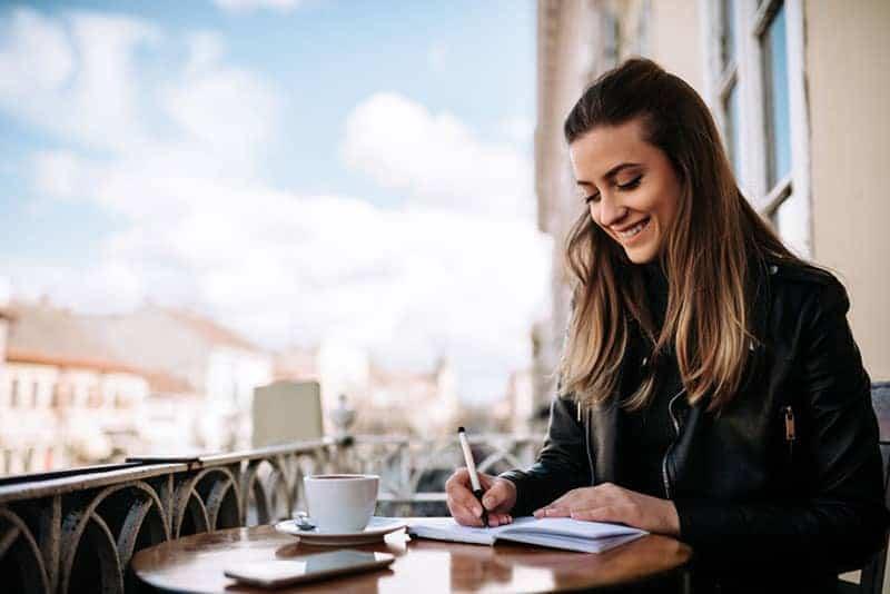kvinna skriver i caffe