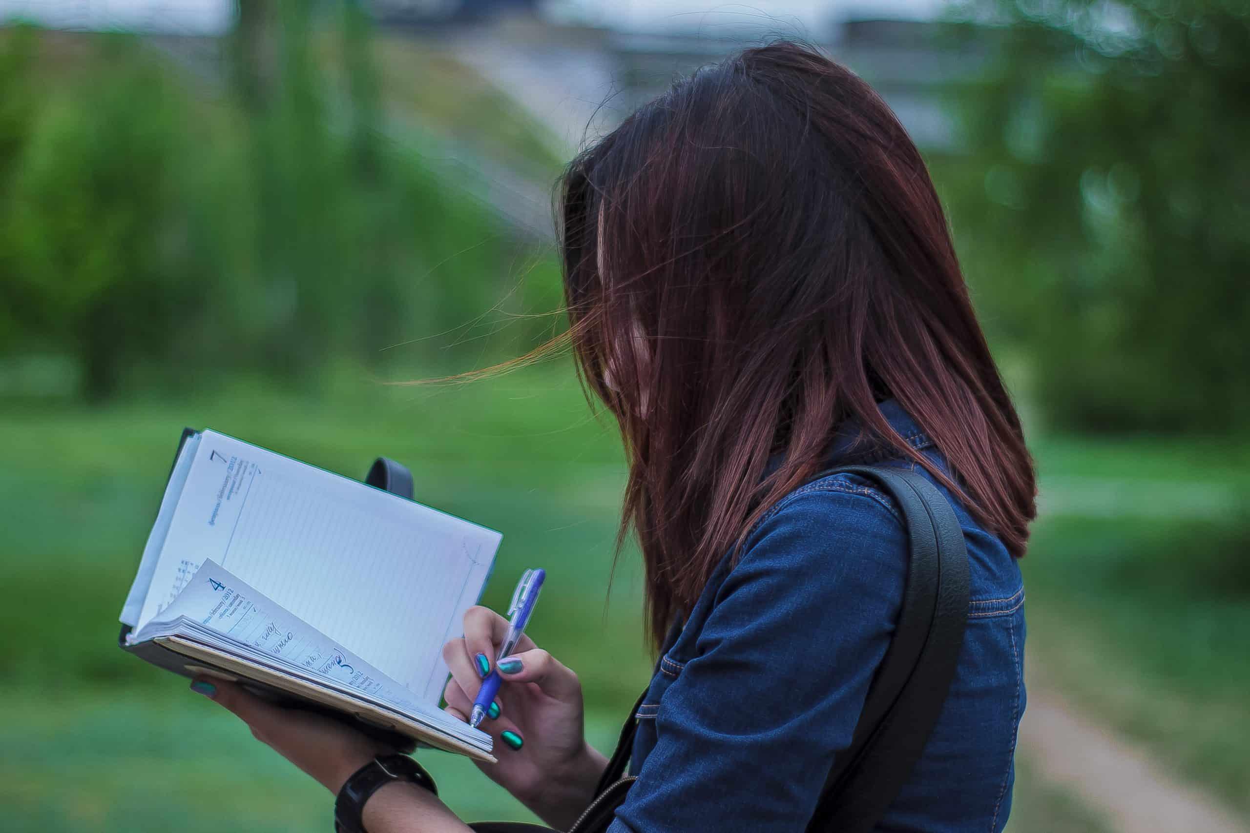 kvinna skriver på anteckningsboken utanför