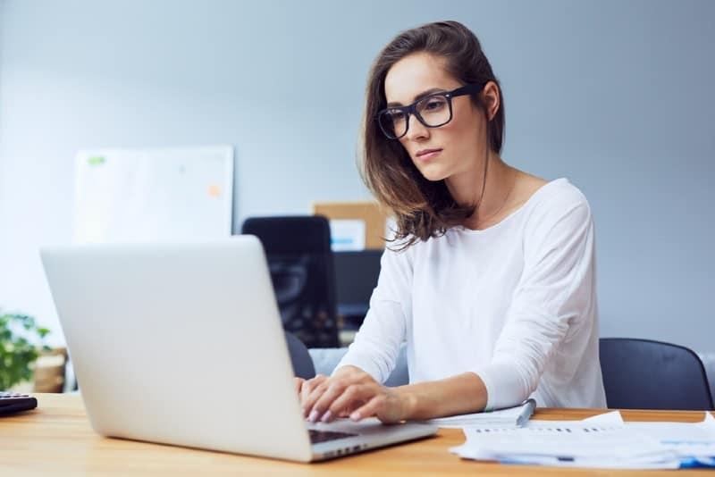 kvinna skriver på bärbar dator