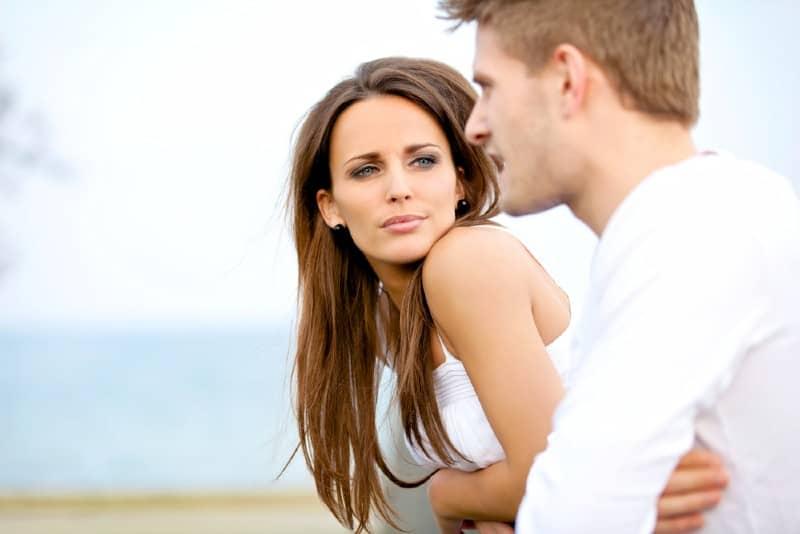 Porträtt av en attraktiv kvinna som allvarligt lyssnar på sin pojkvän på ett datum
