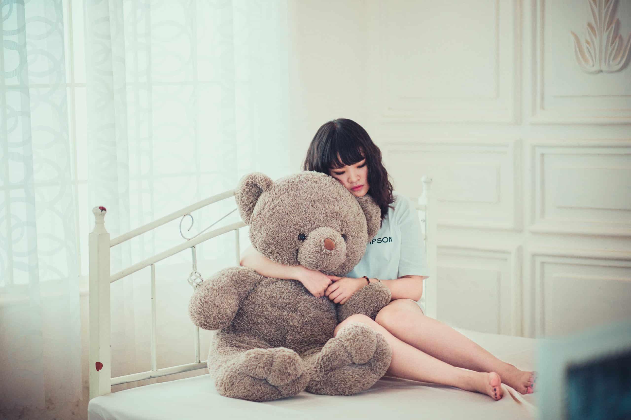 kvinna som kramar björnen i sovrummet