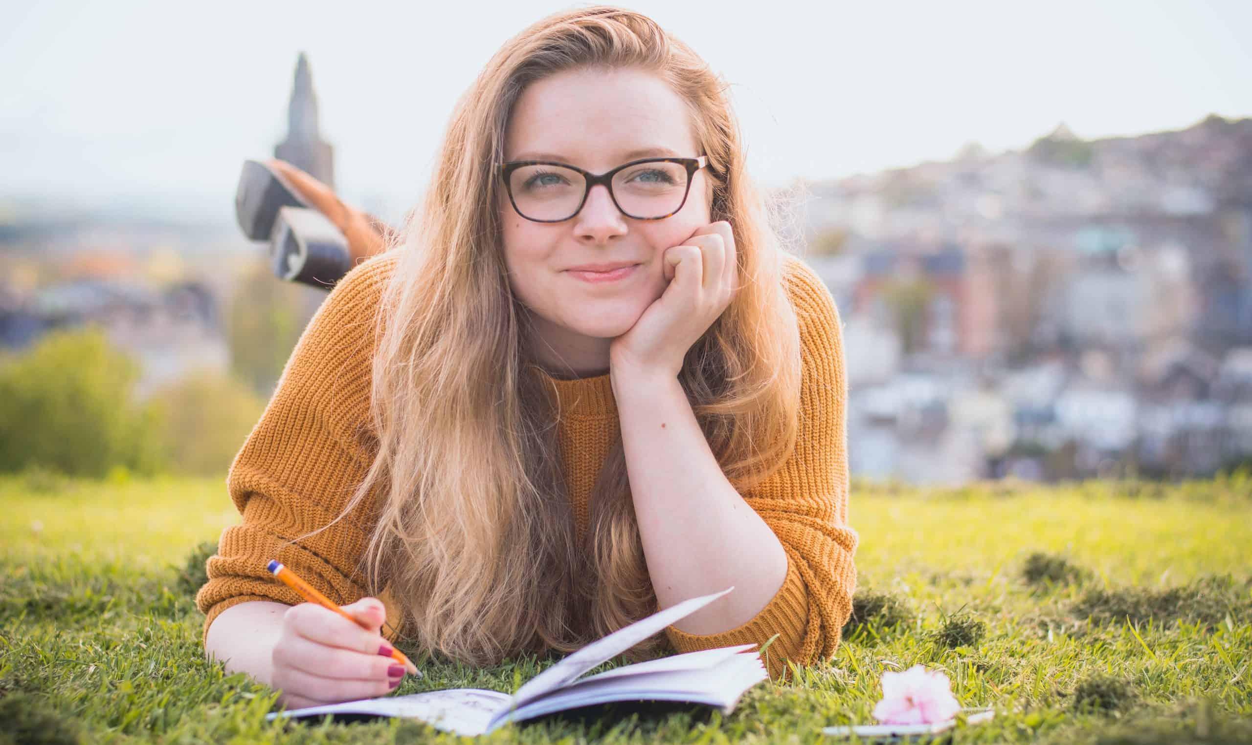 kvinna som ligger på grönt gräs medan du håller blyertspenna