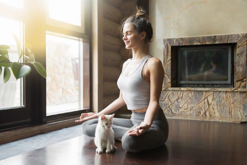 kvinna som utövar yogasammanträde på golvet i lotusställning