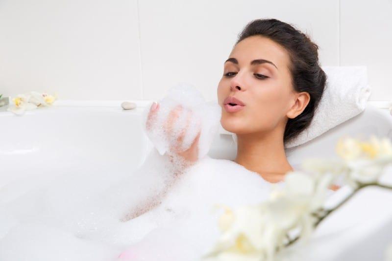 vacker ung kvinna tar bubbelbad
