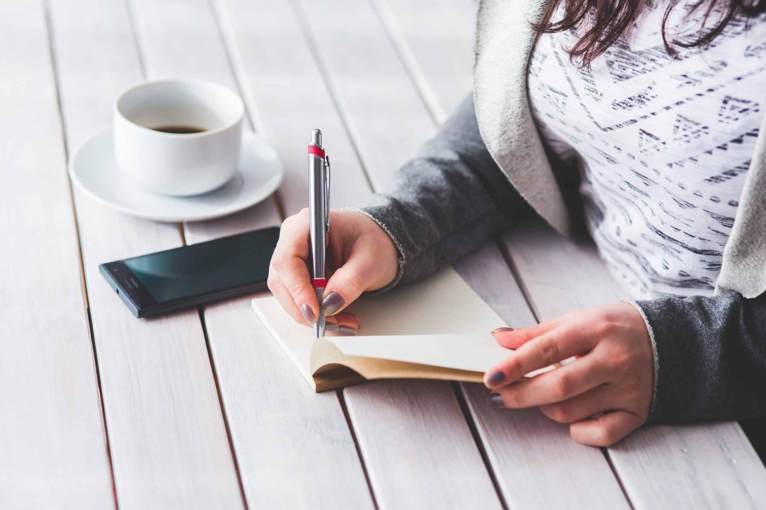 kvinnans hand med en penna anteckning på anteckningsboken