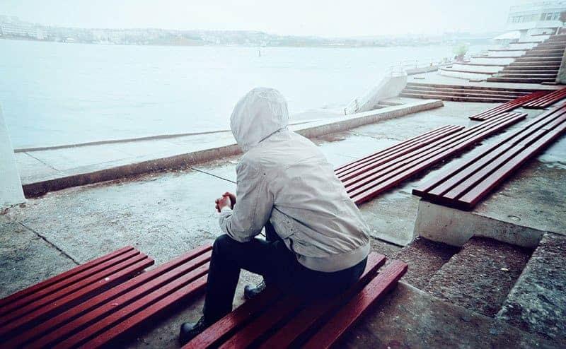 ledsen man sitter ensam utomhus