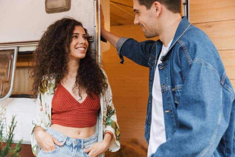 leende par pratar när de står nära huset