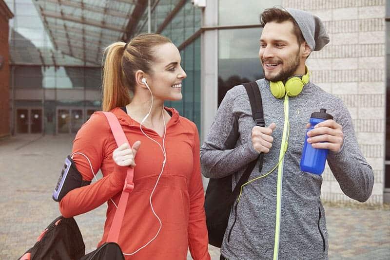 leende par som går till gymmet