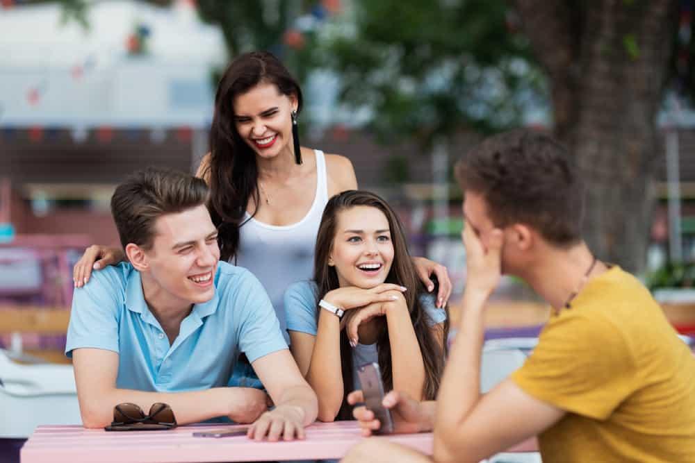 leende vänner sitter och pratar utanför vid bordet