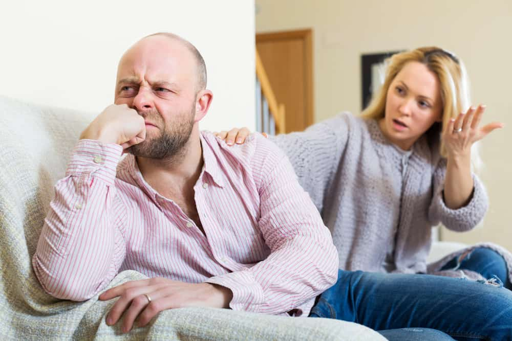 man and woman having quarrel in livingroom
