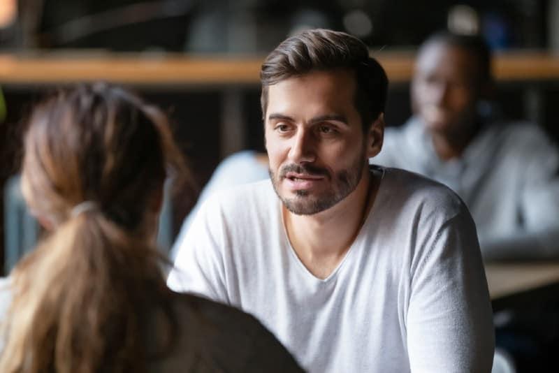 man som har konversation med kvinnaflickvän som sitter vid kafébordet