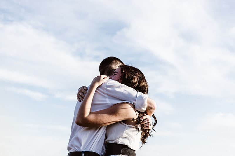 man och kvinna kram med himmel i bakgrunden