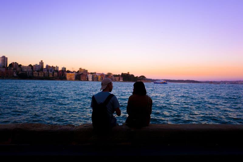 man och kvinna sitter nära vatten och tittar på solnedgången