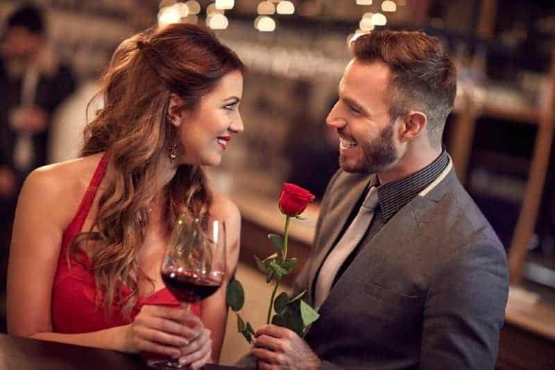 man som håller rosor som står framför kvinnan som håller ett glas och ser varandra