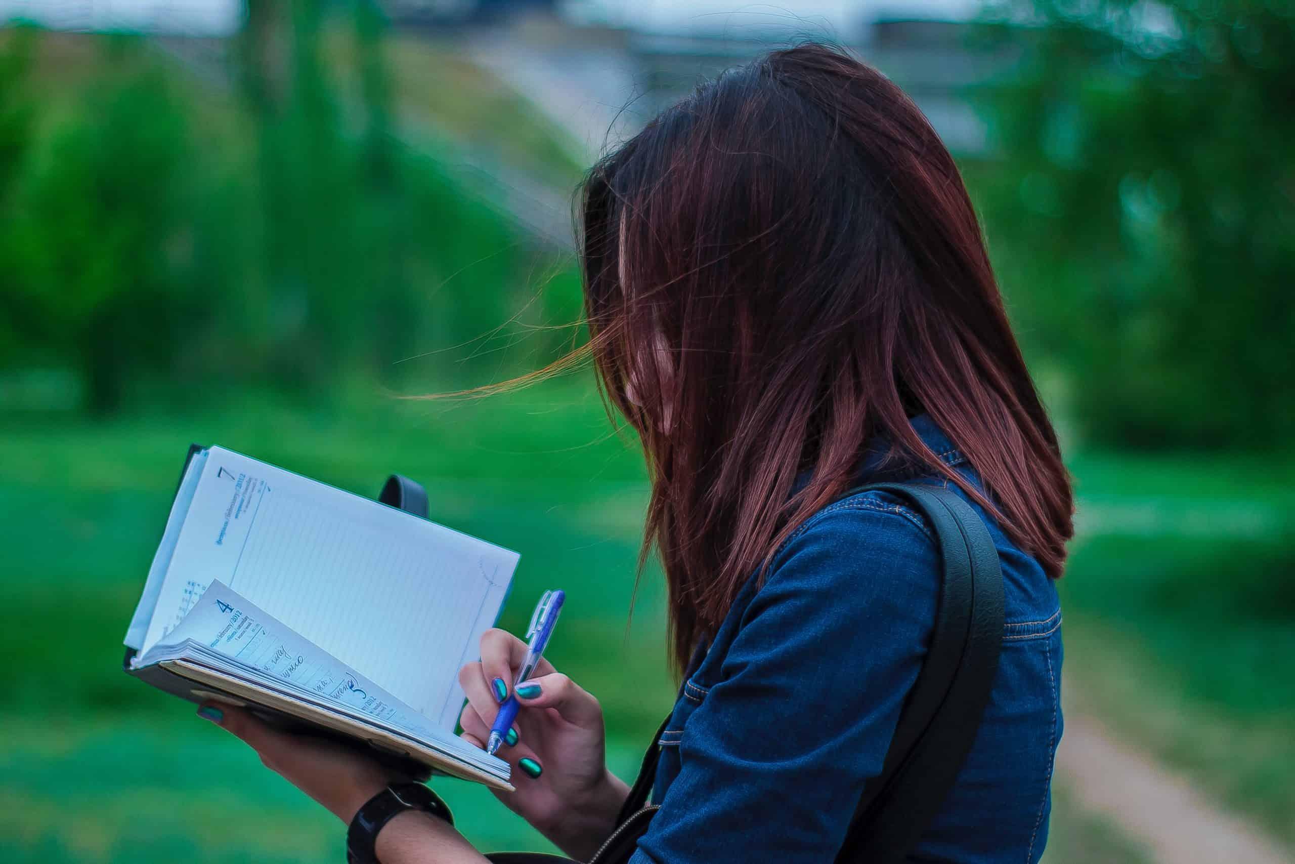 närbild fotografering av en person som skriver på anteckningsbok