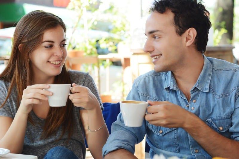 Unga attraktiva par som tycker om ett kaffe på kaféet