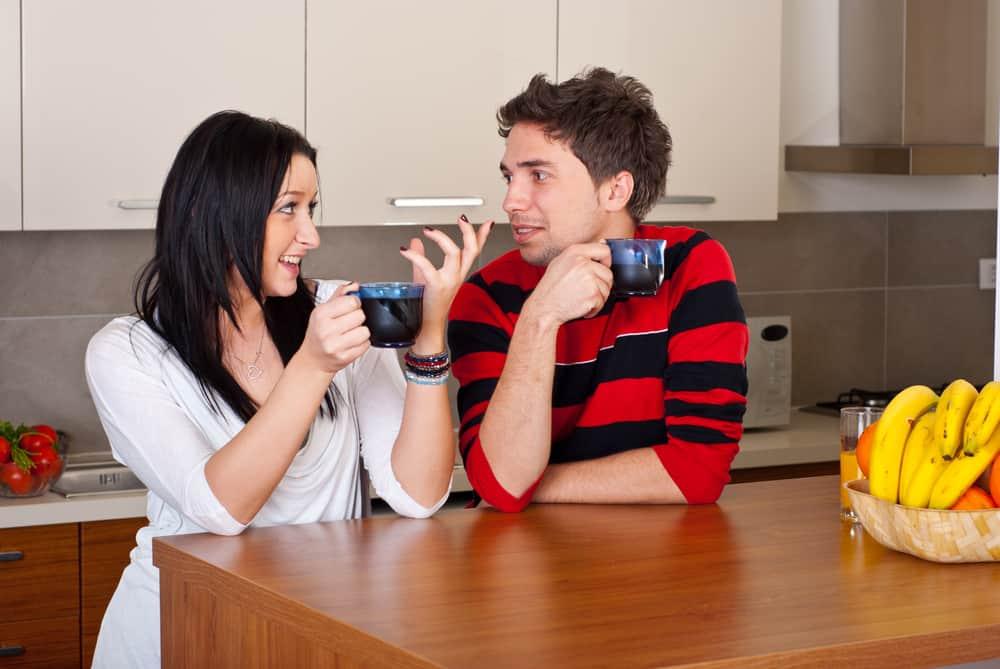 par som har konversation och dricker kaffe på morgonen i deras kök