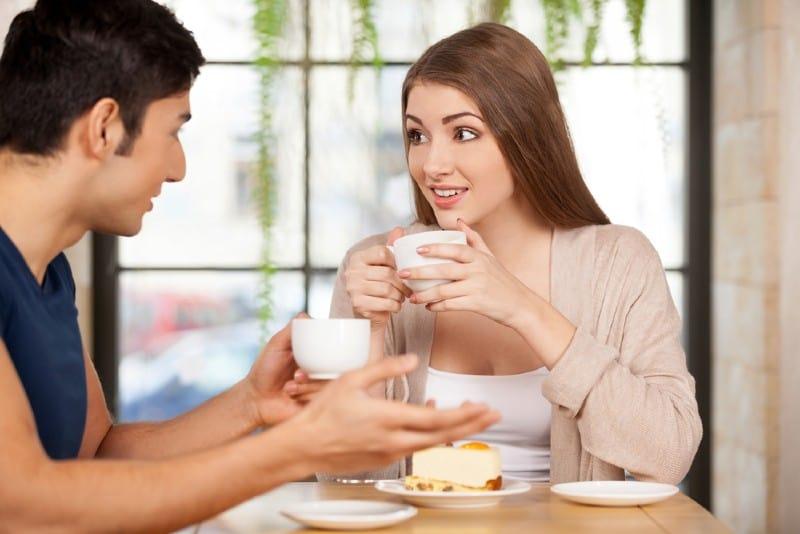 Vackra unga par som tillsammans sitter på restaurangen och dricker kaffe