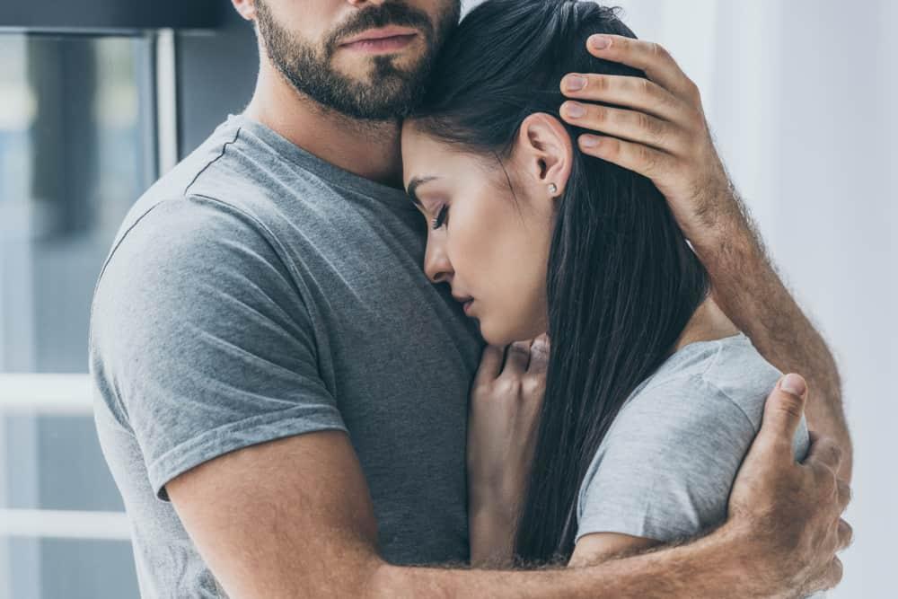 skäggig man som kramar och stödjer den unga sorgliga kvinnan
