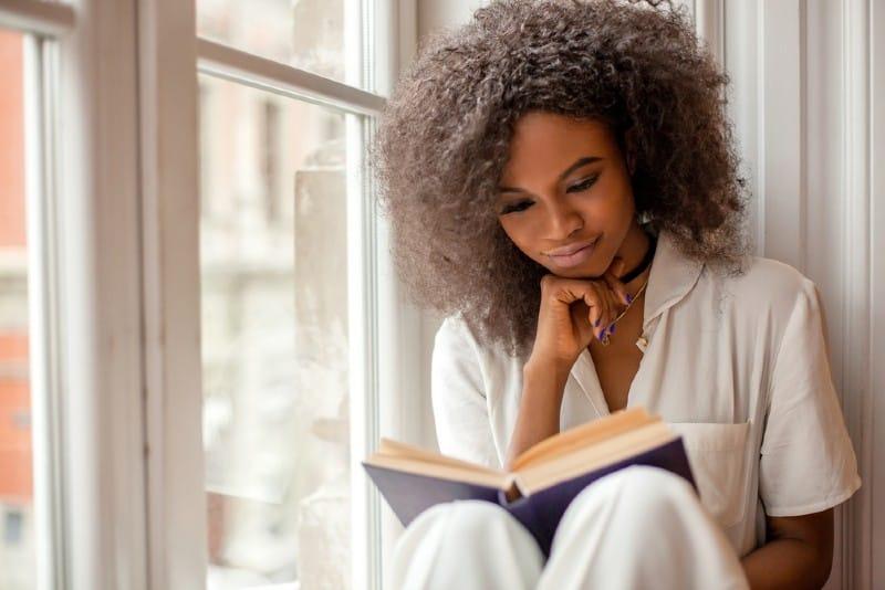 Ganska afroamerikansk flicka som läser ett bok som sitter på fönsterbrädan