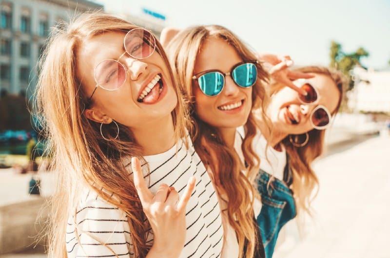 Stående av tre unga vackra leende hipsterflickor i trendiga sommarkläder