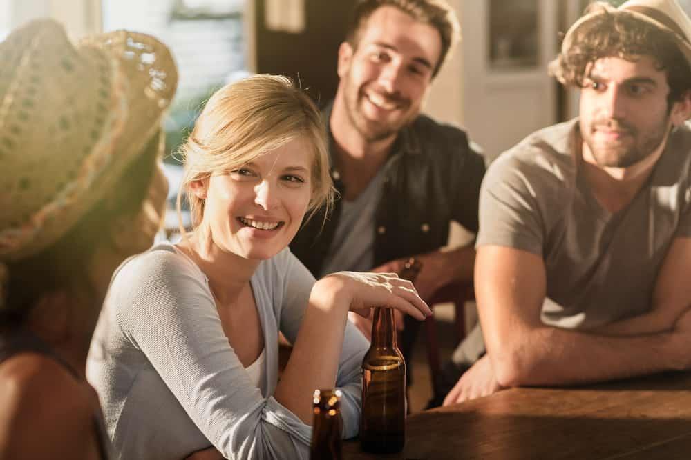 två flickor och två män sitter och dricker öl och pratar