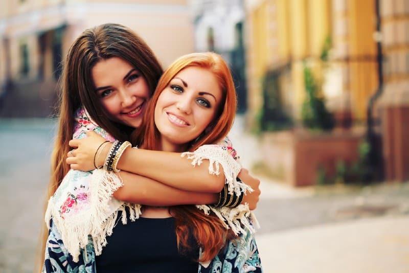 Stående av unga flickor för bästa vänner som kramar varandra